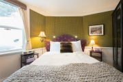 Green Bedroom with upholstered walls and headboard (with multiple reading lights.)