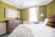 Green Bedroom with upholstered walls, dresser, armoire, original art and more.